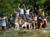Viele Kinder mit Helm stehen im Wasser und winken glücklich in die Kamera.