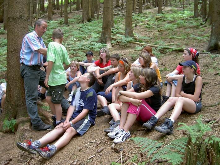 Viele Kinder sitzen auf den Waldboden und hören ihren Führer gespannt zu.