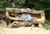 Eine Frau liegt in einem ausgehöhlten Baumstamm.