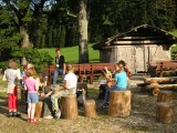 Kinder sitzen auf Holzhockern und haben Spaß.