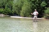 Ein Mann steht im seichten Wasser in der Ybbs und tut Fliegenfischen.